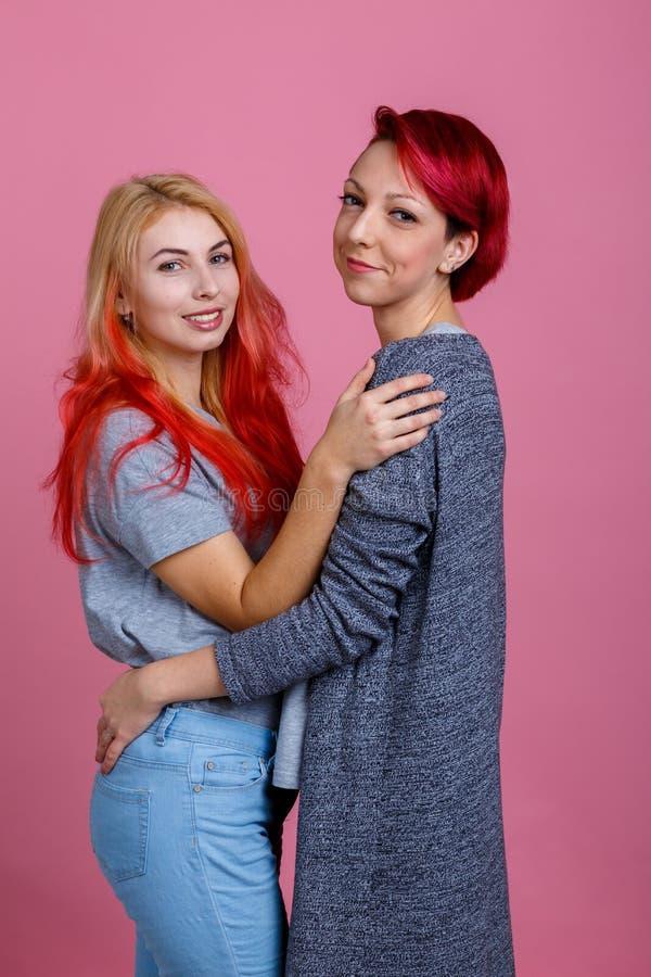 Les lesbiennes se tiennent dans une étreinte sur un fond rose image stock