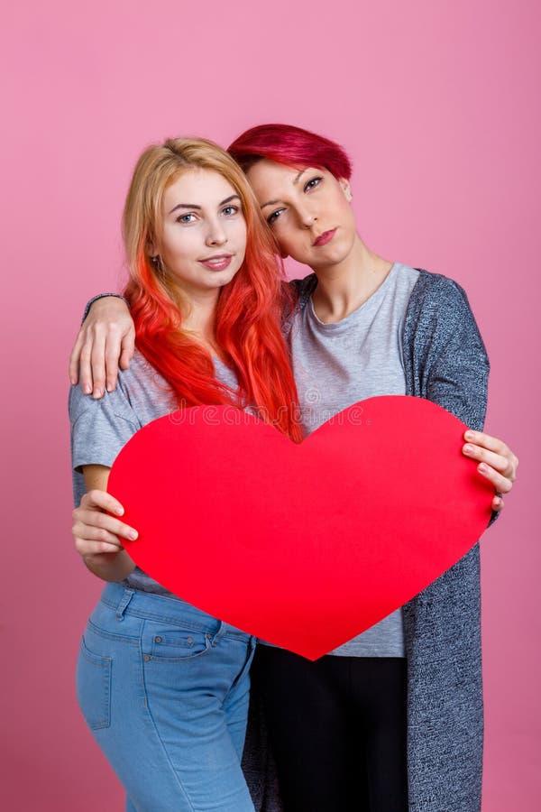 Les lesbiennes tiennent un coeur dans une étreinte sur un fond rose photographie stock libre de droits