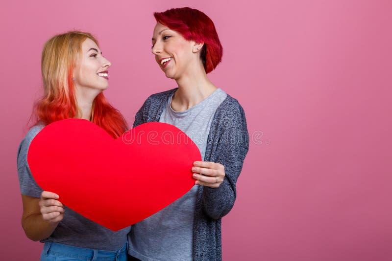 Les lesbiennes tiennent un coeur et regardent l'un l'autre sur un fond rose photos libres de droits