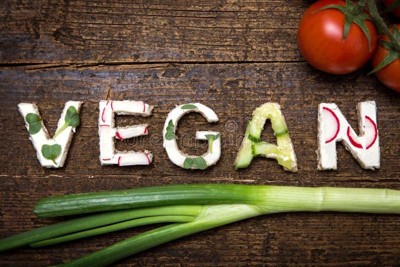 Les lettres des canapes végétaux construit le Vegan de mot images stock