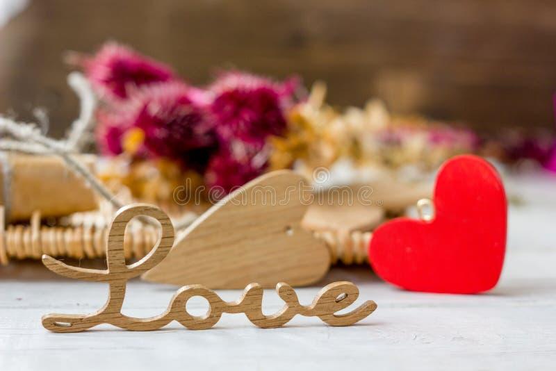Les lettres en bois aiment avec les coeurs rouges et en bois sur la surface blanche photos libres de droits