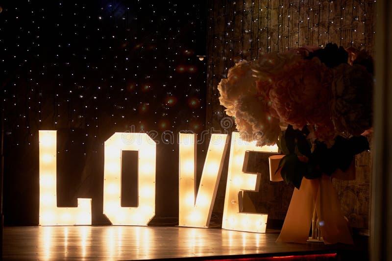 Les lettres rougeoyantes aiment dans la conception d'une partie ou d'une boîte de nuit Jour du `s de Valentine image libre de droits