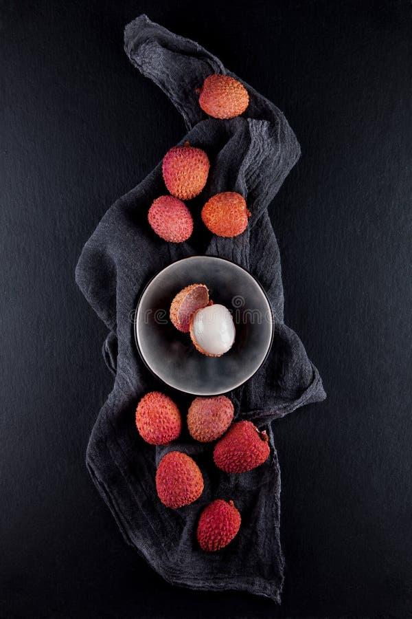 Les litchis exotiques mûrs et vermillons décorés sur une ardoise plaquent le fond de table de cuisine avec la serviette photos stock