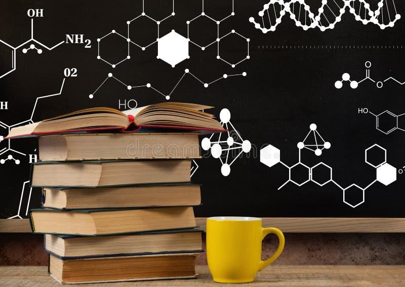 Les livres sur le premier plan de bureau avec des graphiques de tableau noir des dessins de formule de la science diagrams photos libres de droits