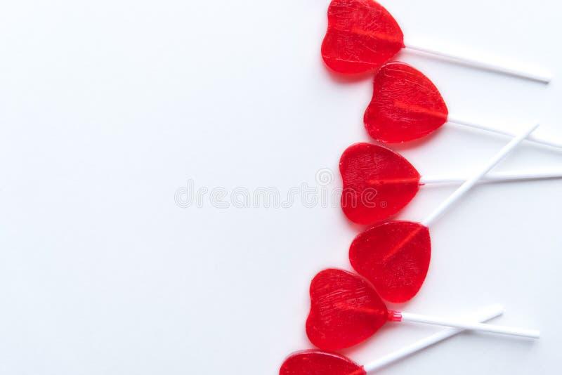 Les lucettes en forme de coeur rouges de Valentine ont dispersé à travers le côté droit du fond blanc photos stock