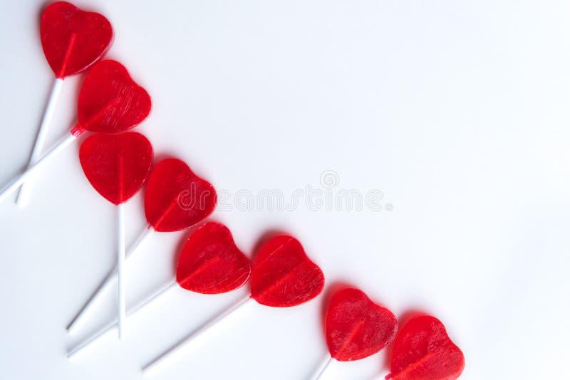 Les lucettes rouges en forme de coeur ont arrangé à travers le côté gauche du fond blanc photos stock