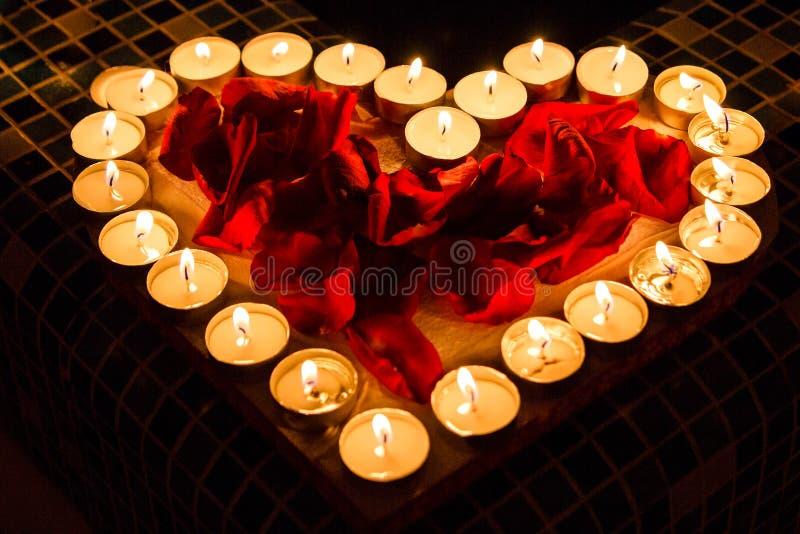 Les lueurs d'une bougie brillent sous la forme du coeur avec des pétales de roses rouges image libre de droits