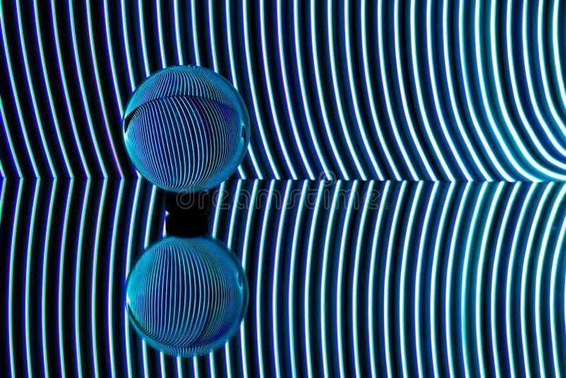 Les lumières bleues ont courbé derrière une sphère transparente Photographie légère de peinture photo libre de droits