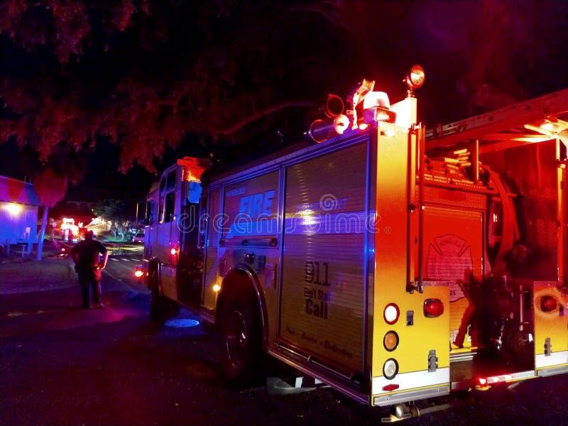 Les lumières de camions de pompiers clignotent sur le campus d'université pendant qu'elles éteignent le feu la nuit image libre de droits