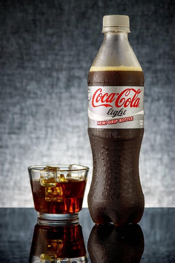 Les lumières de coca-cola dans une bouteille et un verre ont rempli de la glace image stock