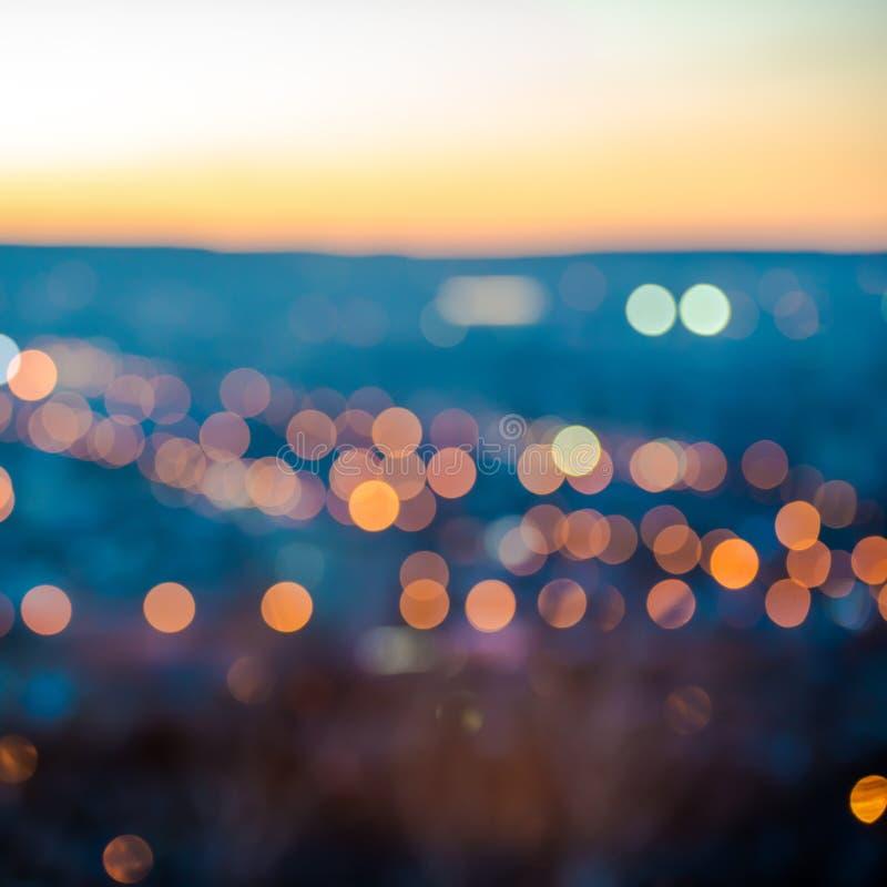 Les lumières de flou de ville soustraient le bokeh circulaire sur le fond bleu photos stock