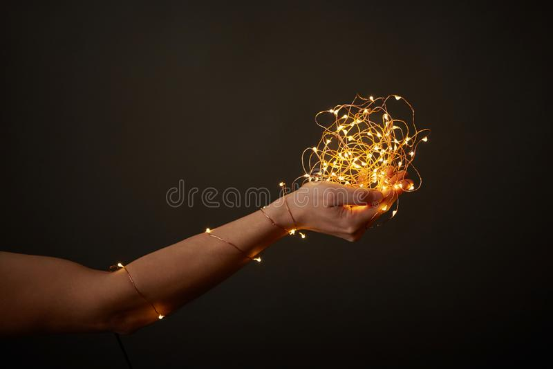 Les lumières de Noël lumineuses jaunes décorent la main d'une fille sur un fond foncé avec l'espace pour le texte photo libre de droits