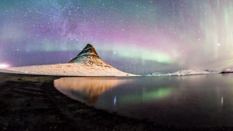Les lumières du nord et la manière laiteuse d'hiver au-dessus de Kirkjufell image libre de droits