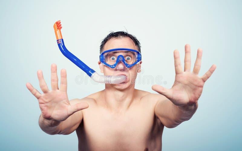 Les lunettes de plongée de port de jeune homme au-dessus du fond bleu d'isolement avec les mains ouvertes faisant le signe d'arrê images stock