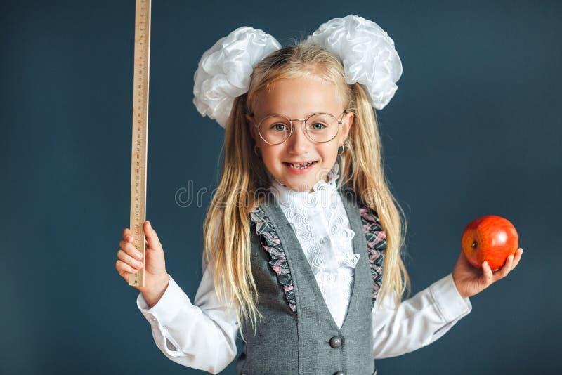 Les lunettes de port drôles de petite fille imite un professeur strict sur le fond bleu regarder l'appareil-photo ?cole de copysp images stock