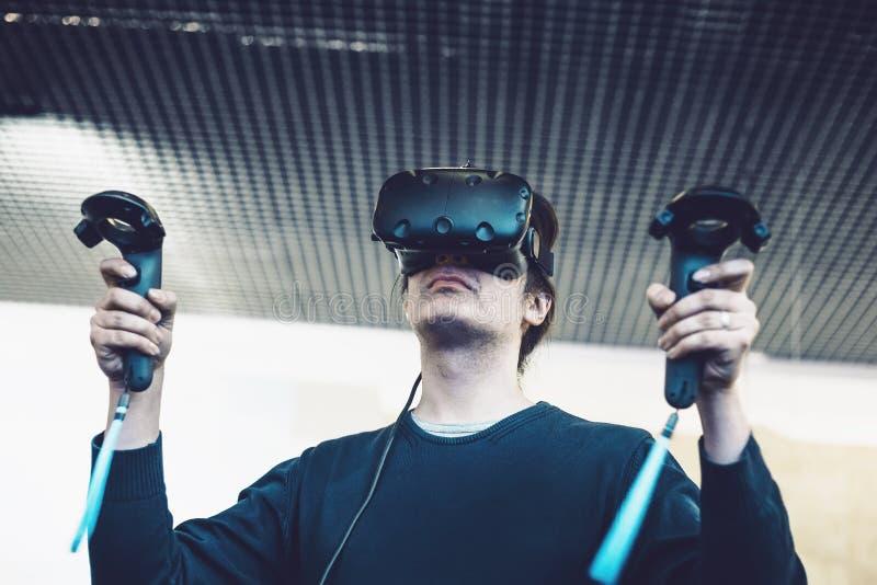 Les lunettes de réalité virtuelle d'utilisation d'homme ou le casque de VR ou le casque, jeu vidéo de jeu avec les contrôleurs sa photographie stock libre de droits