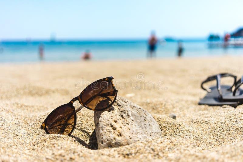 Les lunettes de soleil de Brown se sont penchées vers une pierre sur une plage, bascules électroniques à l'arrière-plan photo libre de droits