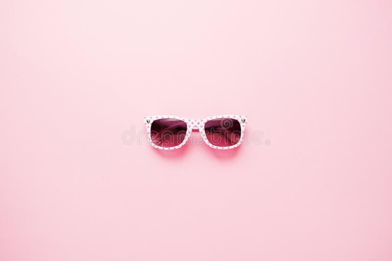 Les lunettes de soleil des enfants pour des filles sur un fond rose Mode d'enfants, concept de vacances d'?t? Configuration minim photos libres de droits
