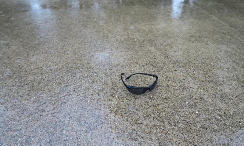 Les lunettes de soleil du ` s de coureur ont laissé tout en courant sous la pluie photos stock
