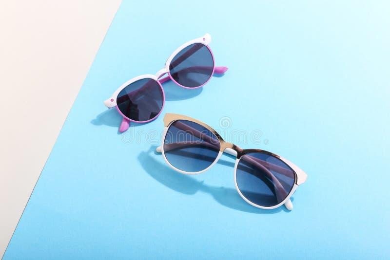 Les lunettes de soleil se trouvent sur un fond coloré moulant une ombre dure, l'art de concept de l'été et la relaxation, minimal image libre de droits
