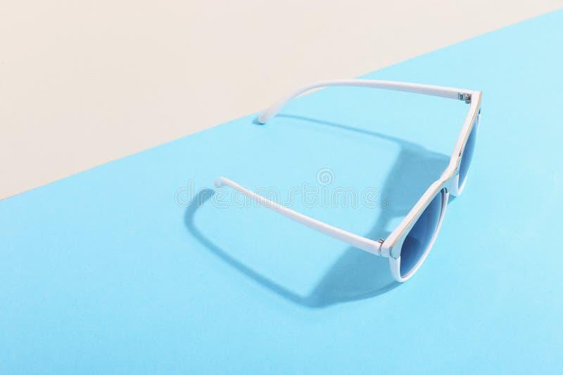 Les lunettes de soleil se trouvent sur un fond coloré moulant une ombre dure, l'art de concept de l'été et la relaxation, minimal photos stock