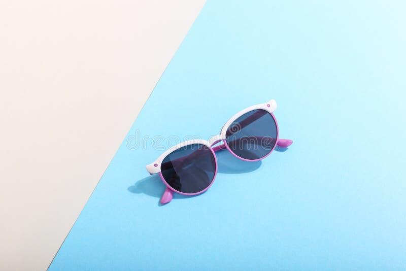 Les lunettes de soleil se trouvent sur un fond coloré moulant une ombre dure, l'art de concept de l'été et la relaxation, minimal photographie stock libre de droits