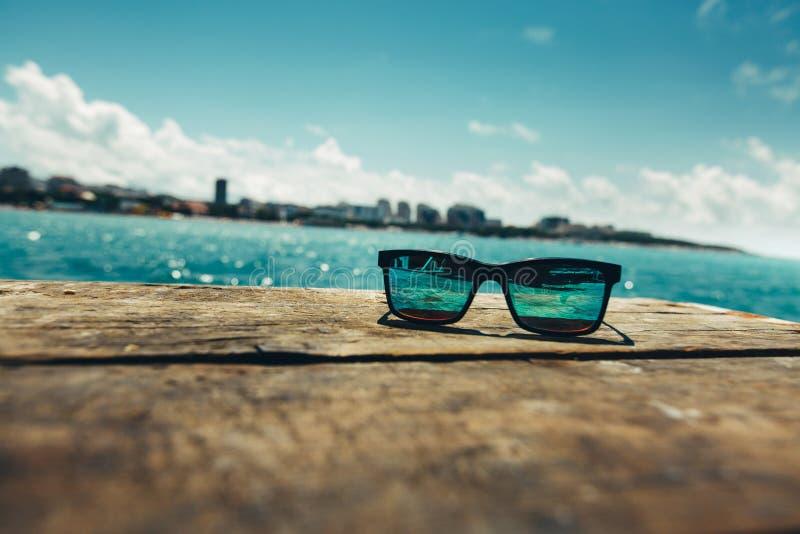 Les lunettes de soleil se trouvent sur une terrasse à l'arrière-plan d'une La de mer d'été photo stock