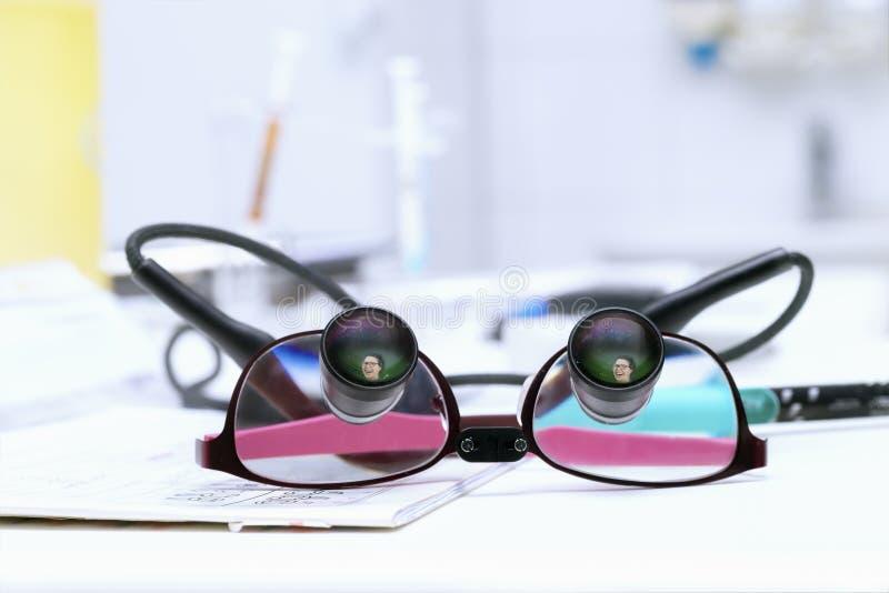 Les lunettes du dentiste spécial avec la réflexion du jeune wom smiing photos stock