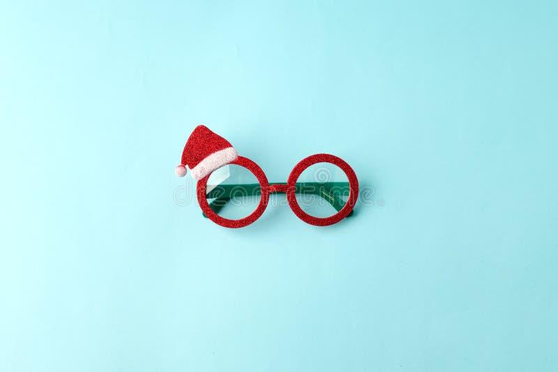 Les lunettes Noël du Père Noël sur fond bleu Fête de mascarade nouvelle année de drôles de lunettes de soleil, une idée de vacanc photos stock