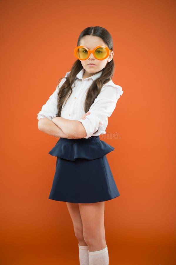 Les lunettes sont plus que juste des lunettes Petite fille adorable portant les lunettes de fantaisie sur le fond orange Petit en image libre de droits