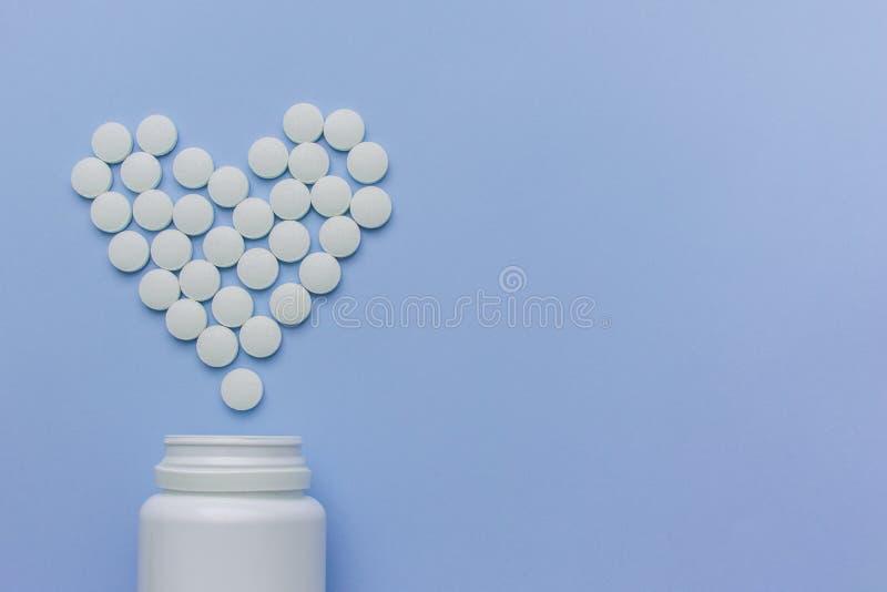 Les médecines sont les pilules blanches et rondes avec un noyau, sur un fond pourpre image libre de droits