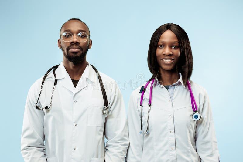 Les médecins afro-américains heureux de femelle et de mâle f sur le fond bleu image stock