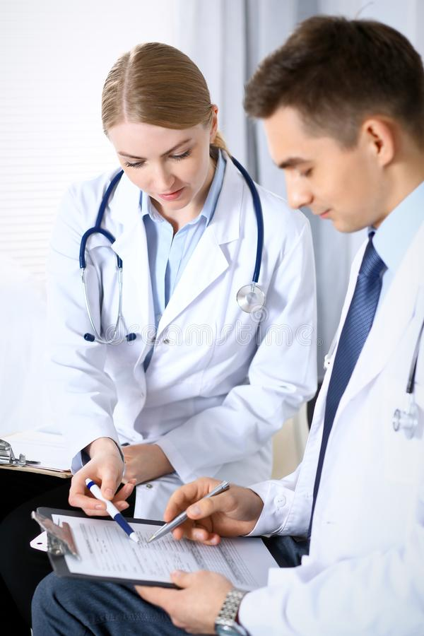 Les médecins discutant le médicament enregistre la forme ou l'étude à la conférence médicale Soins de santé, assurance et concept photo stock