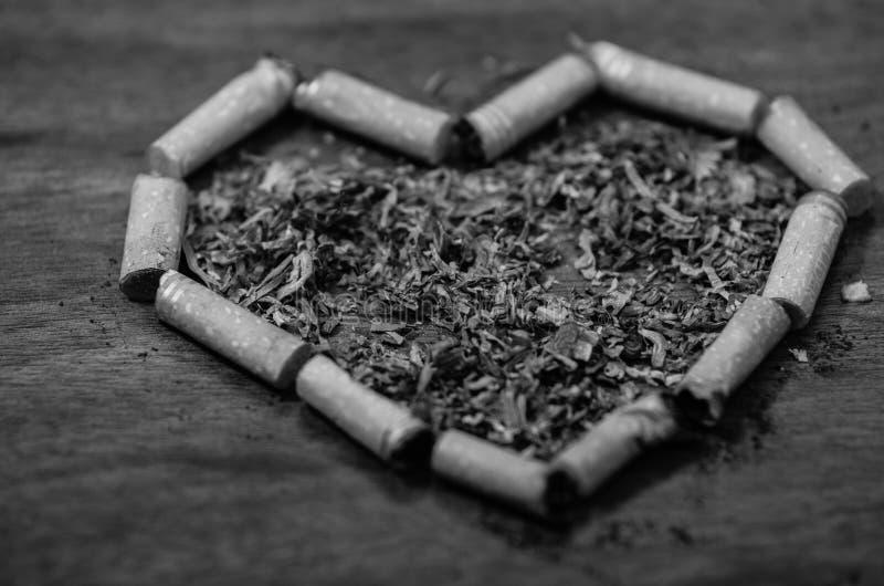 Les mégot formés dans un coeur se trouvant sur la surface en bois, tabac ont écarté autour du milieu, vu d'en haut, noir et image stock