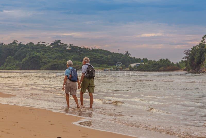 Les ménages mariés des personnes âgées sur la plage sur l'océan étayent photos stock