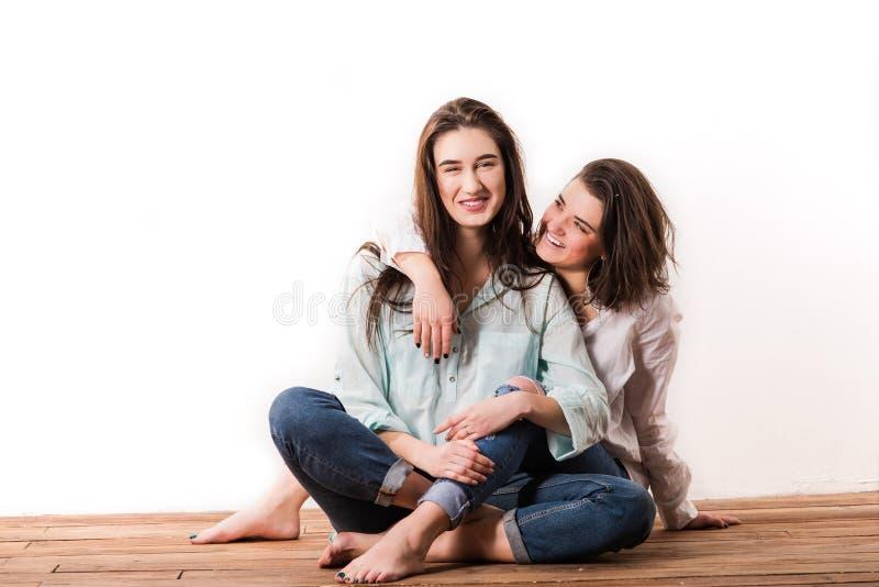 Les mêmes couples heureux de sexe se reposant sur le plancher en bois photos stock
