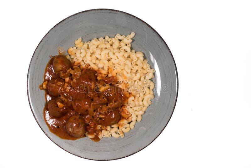 Les macaronis avec les boulettes de viande et le ketchup dans un plat isoated sur le fond blanc photo stock