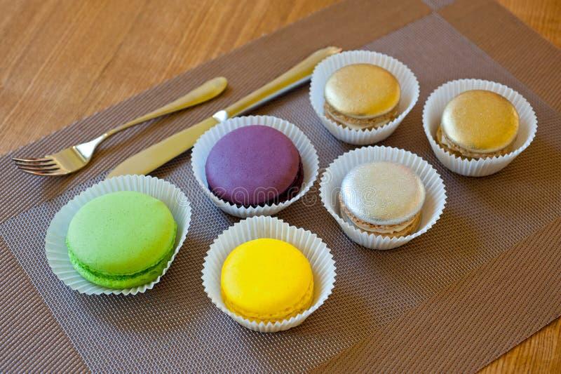 Les macarons de différentes couleurs lumineuses en papier forme le tir en gros plan à côté des couverts image libre de droits
