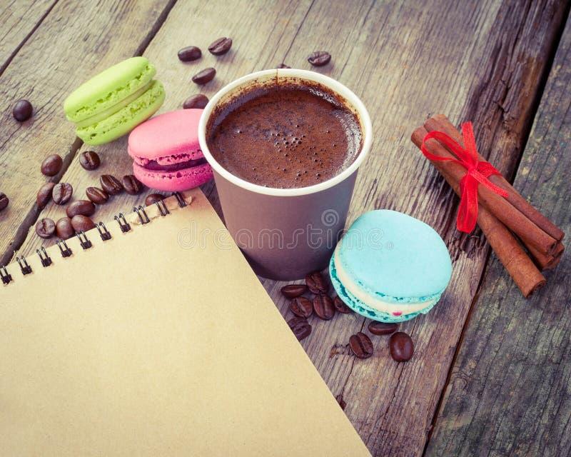Les macarons, la tasse de café d'expresso, les bâtons de cannelle et le croquis réservent photos libres de droits