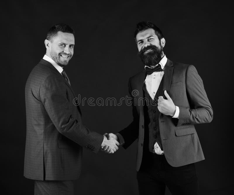 Les machos dans les costumes classiques concluent l'accord d'affaires photographie stock libre de droits