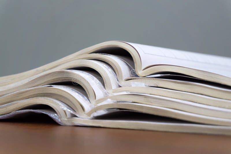 Les magazines ouvertes se trouvent sur l'un l'autre sur une table brune, documents sont en gros plan empilé photo stock