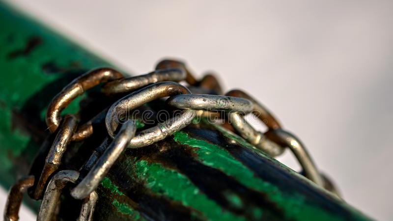 Les maillons de chaîne en acier enroulent autour du tuyau d'acier image stock