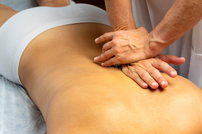 Les mains appliquent une pression le long de la colonne vertébrale à la patiente images libres de droits