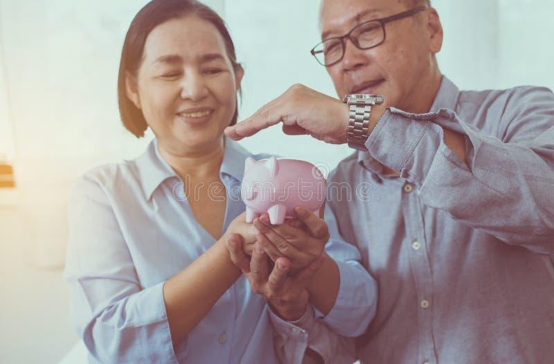 Les mains asiatiques supérieures de couples couvrent à la tirelire pour la retraite ensemble, sauvant le concept d'argent images libres de droits