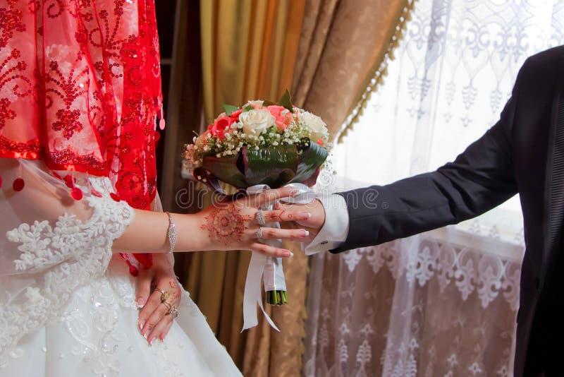 Les mains avec des fleurs de mariage, marié met sur des fleurs d'un mariage à la jeune mariée, habillant les fleurs les épousant, photos libres de droits