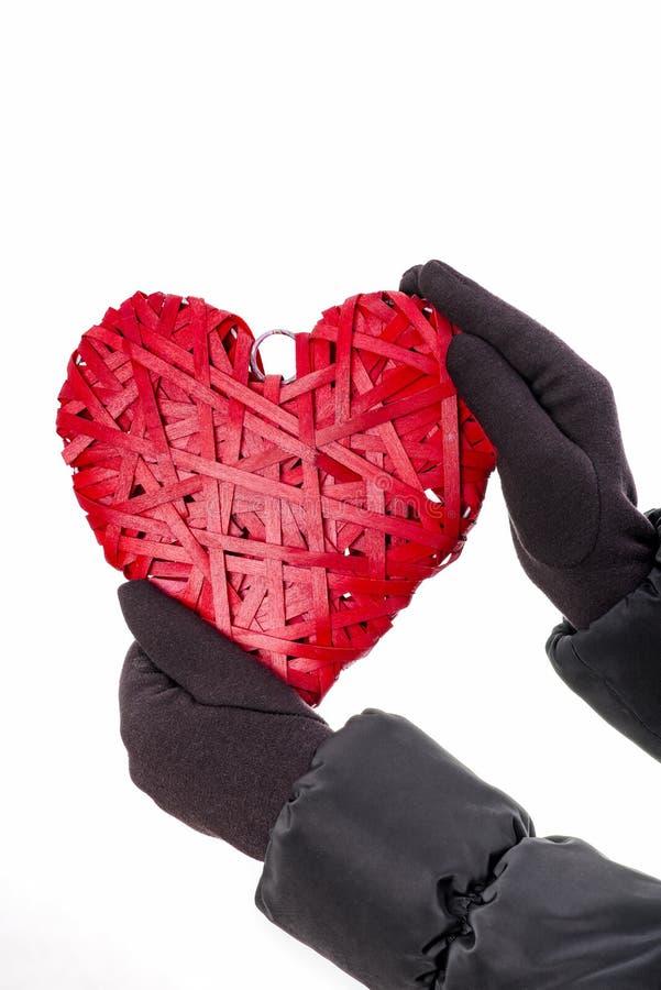 Les mains avec des gants tiennent le coeur en osier rouge photo stock