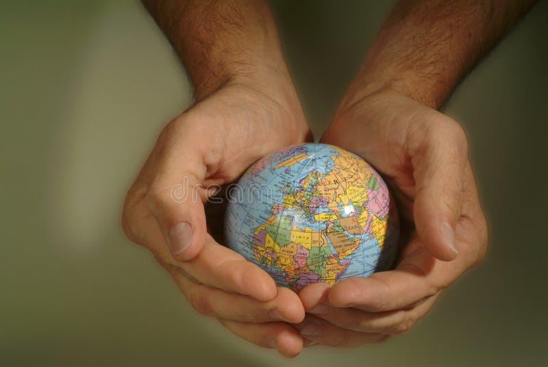 Les mains bercent le petit globe photos libres de droits