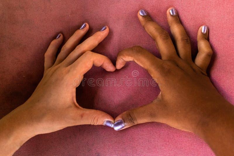 Les mains blanches et noires des amies forment un coeur des doigts contre le racisme photographie stock