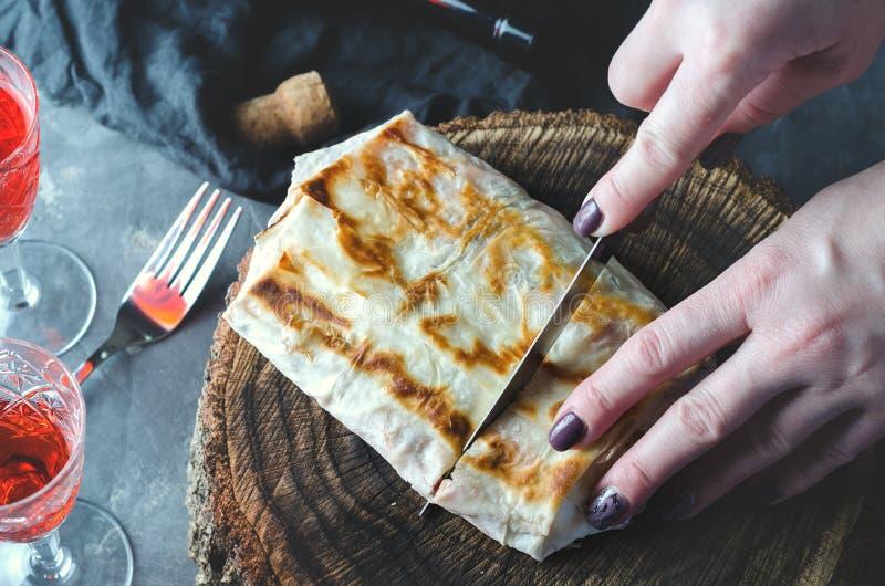 Les mains circoncies d'une femme sont coupées avec un couteau de lavash de pain pita sur un chanvre en bois photographie stock libre de droits