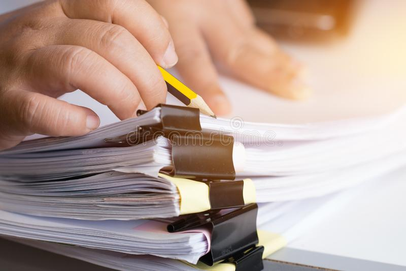 Les mains d'homme d'affaires recherchant les piles documents non finies de fichiers papier sur le bureau les papiers de rapport,  images libres de droits